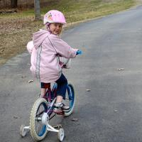 Kira riding bicycle up the driveway